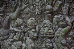 Wall with reliefs and moss in Bali Indonesia. With monkeys Stock Images