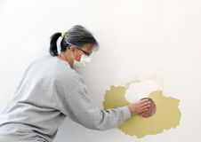 Wall repair. Woman construction worker wearing a mask is sanding a patch on a wall Stock Photography