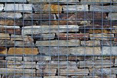 Wall of river stones sustained by metallic net Royalty Free Stock Image