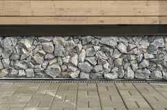 Wall of rough broken grey stones and wooden planks stock photography