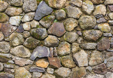 Wall of round and crushed stone with moss. Wall of large round and crushed colored stone covered with moss and clay Stock Image