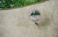 Wall with a round mirror. Wall in front of green trees with a round mirror stock photography