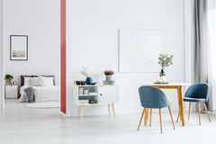 Wall separating open space interior. White wall separating an open space apartment interior - bright living and dining room and a cozy bedroom Royalty Free Stock Photo