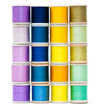 Wall of sewing threads. Stacks of vintage sewing threads isolated on white with shades of purple, blue, yellow and green Royalty Free Stock Photography