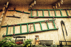 The wall of shed with ladders, various tools and dried corn Stock Image