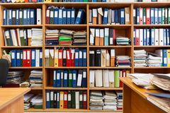 Wall from shelves with colourful file binders, an office room with papers and documents Royalty Free Stock Image