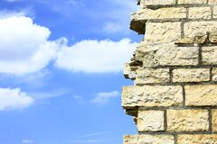 Wall and sky. Part of a broken wall, in the background blue sky with some clouds Royalty Free Stock Photos