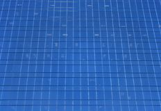 Wall of a skyscraper. Glass-windowed wall of skyscraper. Blue windows background stock image