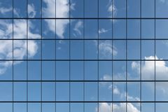 Wall of skyscraper under blue sky with clouds. Wall of modern business skyscraper with blue windows in day sunlight under blue sky with clouds raising to the sky Royalty Free Stock Image