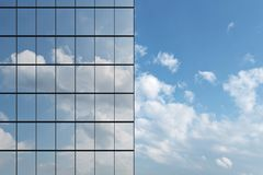 Wall of skyscraper under blue sky with clouds. Wall of modern business skyscraper with blue windows in day sunlight under blue sky with clouds raising to the sky Royalty Free Stock Photo