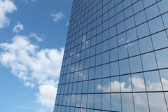 Wall of skyscraper under blue sky with clouds. Wall of modern business skyscraper with blue windows in day sunlight under blue sky with clouds raising to the sky Stock Photography