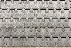Wall of small antique Buddha images. Portrait of a antique buddha statue Royalty Free Stock Image