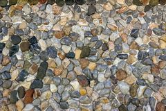 Wall of small multicolored pebbles. The stone surface of the wa Royalty Free Stock Photography