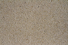 Wall of small stones texture. Pebbles and sand wall texture. Small stones wall background for design with copy space Stock Image