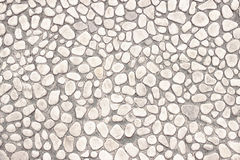 Wall of small stones, white background  light design Stock Images