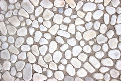Wall of small stones, white background  light design Royalty Free Stock Image