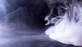 The wall of smoke. Spread out the vape smoke on the black table Royalty Free Stock Photography