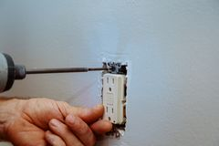 Tightening a on an Electrical Outlet. Wall socket installation a on an electrical outlet royalty free stock photos