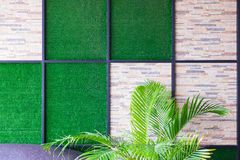 Wall of stone and artificial grass background with metal frame a stock photos