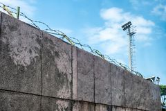 Wall stone with coils barbed wire and security camera royalty free stock photography