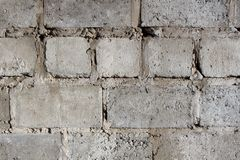 Wall of a stone house from rough concrete blocks with pieces of cement. Wall of a stone house from rough concrete blocks close-up, background image stock photo