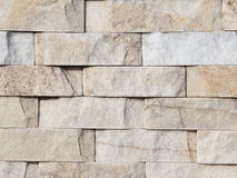Wall stone light gray. Gray wall made of natural rough stone with light dents, bumps and spots Stock Photography