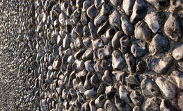 Wall of stones. A wall of small flint stones catches the light Stock Photography