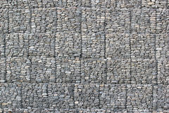 Wall of stones behind metal wire mesh Royalty Free Stock Images