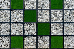 Wall of stones and green grass. In square pattern royalty free stock image