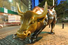 Wall Street Bull. Charging Bull, also referred to as the Wall Street Bull, with a Daily News delivery truck driving by in Lower Manhattan Royalty Free Stock Images