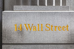 Wall Street golden inscription on a building gray stone wall. Royalty Free Stock Images