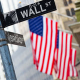 Wall street, New York, USA. Wall street sign in New York with American flags and New York Stock Exchange in background Stock Photos