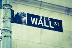 Wall Street road sign corner of NY Stock Exchange. Wall Street road sign in the corner of New York Stock Exchange, Manhattan an icon of global investment Stock Photo