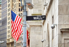Wall Street sign with American flag in distance, NYC, USA. Royalty Free Stock Photography