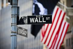 Wall street sign with American flag in the Financial District of Lower Manhattan royalty free stock photo