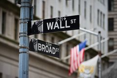 Wall street sign with American flag in the Financial District of Lower Manhattan royalty free stock image