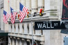 Wall Street  sign with american flag. NEW YORK, NY - NOVEMBER  28: Wall Street  sign with american flag  and with New York Stock Exchange USA seen in November 28 Royalty Free Stock Images