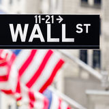 Wall street sign in New York City with american flags on the bac Stock Photography