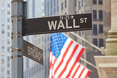 Wall Street sign and US flag in New York Stock Photos