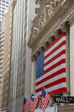 Wall Street, street sign, with US flag. In New York City Stock Photos