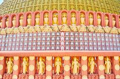 The wall of stupa of Sitagu International Buddhist Academy. With ornate decorations - plaster pannels, relief patterns, large gilt vases and wall statues of royalty free stock photos