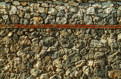 Wall surface with uneven cracked real stones and red bricks. Texture stock image
