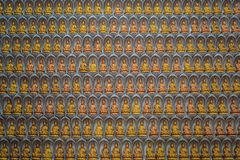 The wall in the temple is filled with buddhas. Religion Buddhism concept. Texture, background Buddhism.  royalty free stock images