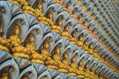 The wall in the temple is filled with buddhas. Religion Buddhism concept. Texture, background Buddhism.  stock photography