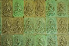 The wall in the temple is filled with buddhas. Religion Buddhism concept. Texture, background Buddhism.  stock image