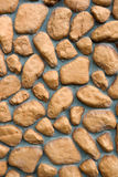 Wall texture of big stones. Building wall texture made of big rough yellow stones pressed into cement Royalty Free Stock Images