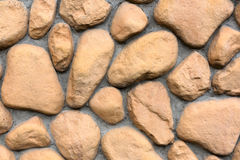 Wall texture of big stones. Building wall texture made of big rough yellow stones pressed into cement Stock Image