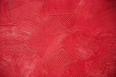 Wall texture with a deep circular dabs of putty, covered with red paint. Royalty Free Stock Image