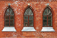 A wall with three windows Stock Image