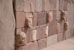 Wall in Tiahuanaco  with stone faces. Wall with stone faces in Tiahuanaco Bolivia Royalty Free Stock Photos